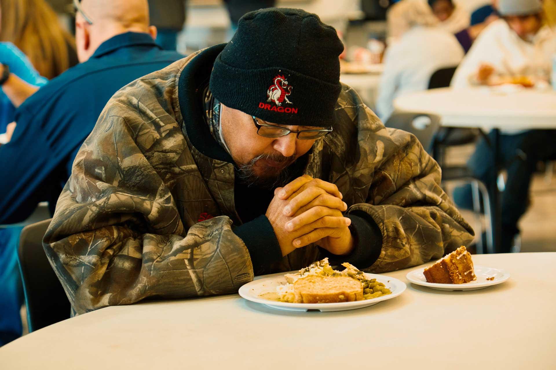 man praying before meal