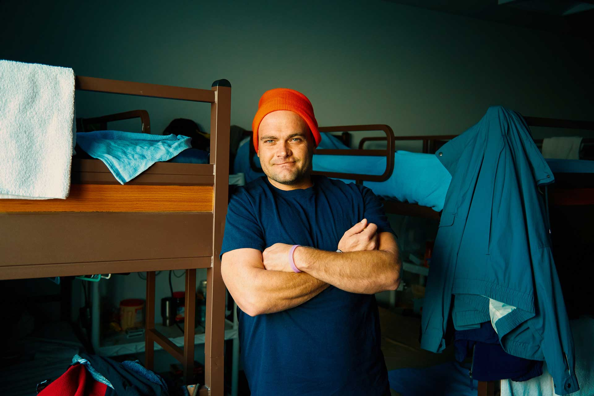 man next to bed arms crossed