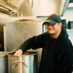 man stirring pot